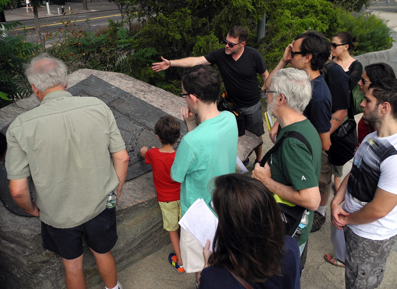 Tour guide Justin Rivers explains the 1660 map at Peter Minuit Plaza.